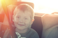 Cheerful child with buttoned belt in a car. On a sunset Stock Photography