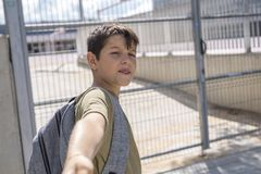 Cheerful child carrying his backpack standing in front of the sc stock photo