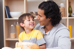 Cheerful child eating bread with his father Royalty Free Stock Photos