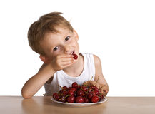 Cheerful child eats a cherry Royalty Free Stock Photo