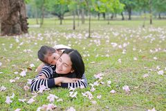 Cheerful child girl cuddle her mom lying on green field with fully fall pink flower in the garden outdoor. Happy loving family.  stock image