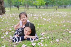 Cheerful child girl cuddle her mom lying on green field with fully fall pink flower in the garden outdoor. Happy loving family.  royalty free stock images