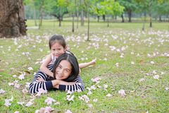 Cheerful child girl cuddle her mom lying on green field with fully fall pink flower in the garden outdoor. Happy loving family stock photography