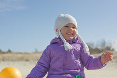 Cheerful child girl outdoor. Cheerful child girl dressed in purple coat and white hat in springtime Royalty Free Stock Photography