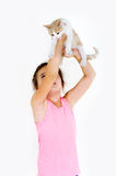 Cheerful child girl plays with a little kitten on a light background Stock Photo