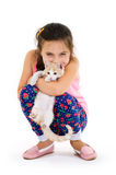 Cheerful child girl plays with a little kitten on a light background Royalty Free Stock Photography