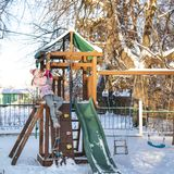 A cheerful child girl plays on the Playground on snowy winter day stock photos
