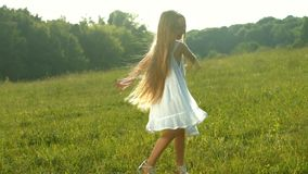 Cheerful child. Girl in white dress dancing on a green meadow. Cheerful child stock video