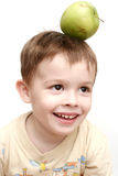 The cheerful child with a gree. N apple on a head Stock Photos