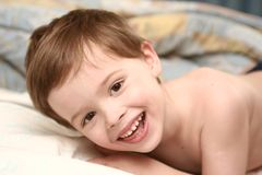 The cheerful child lays stock photos