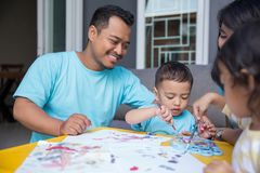 Child painting water color with dad. Cheerful child painting with water color at home with dad royalty free stock photo