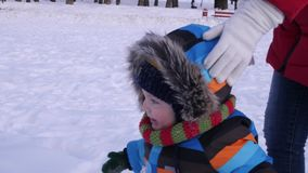 Year old baby boy in warm snow suit walking and having fun in winter park. Cheerful child playing in the first snow in. Cheerful child playing in the first snow stock video