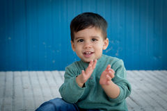 Cheerful child playing palms on the street Stock Images
