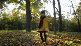 Cheerful child, portrait of beautiful little girl having fun outdoor playing with yellow leaves in autumn park