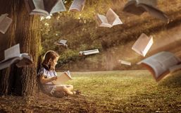 Cheerful child reading an interesting book. In a summer park stock photo
