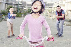 Cheerful child riding bicycle outdoors Stock Photos