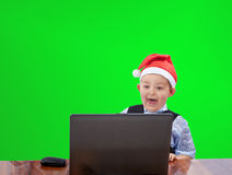 Cheerful child in a Santa Claus cap looking at a laptop Royalty Free Stock Images