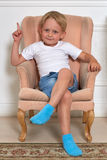 Cheerful child sitting on armchair. Happy little boy is sitting on the soft armchair in the room Stock Photos