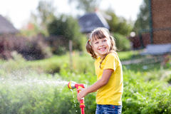 Cheerful child watering plants from hose spray in Royalty Free Stock Image