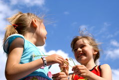 Cheerful children. Two laughing girls against the sky Stock Images