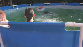 Cheerful children bathe in pool in summer  day stock footage