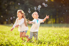 Cheerful children chase bubbles. Cheerful children run and chase bubbles in nature Stock Photo