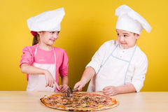Cheerful children cook pizza Royalty Free Stock Photo