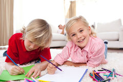 Cheerful children drawing lying on the floor Royalty Free Stock Photos