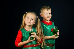Kids fun in green costumes on St. Patrick`s day. Cheerful children in green suits with a glass of green drink on St. Patrick`s day Stock Images