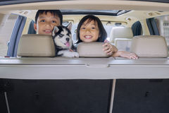 Cheerful children and husky dog in the car Stock Photography