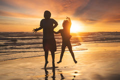 Cheerful children jumping on beach Stock Images