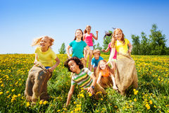 Cheerful children jumping in sacks play together. Cheerful children jumping in sacks playing together in summer Royalty Free Stock Photo