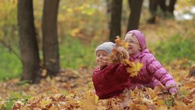 Cheerful children playing in leaves pile in autumn stock footage