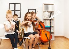 Cheerful children playing musical instruments. Together in musical school Stock Images
