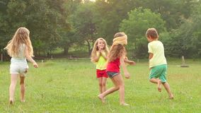 Cheerful children playing tag with clapping on the grass on a summer day. Slow motion