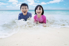 Cheerful children playing water on beach Royalty Free Stock Image