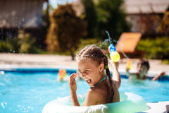 Cheerful children playing waterguns, rejoicing, jumping, swimming in pool. royalty free stock photos