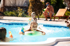 Cheerful children playing waterguns, rejoicing, jumping, swimming in pool. Copy space Stock Image
