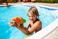 Cheerful children playing waterguns, rejoicing, jumping, swimming in pool. Copy space Royalty Free Stock Images