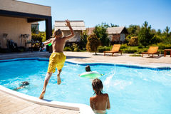 Cheerful children playing waterguns, rejoicing, jumping, swimming in pool. Copy space Royalty Free Stock Photos