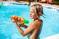 Cheerful children playing waterguns, rejoicing, jumping, swimming in pool. Copy space Royalty Free Stock Photo