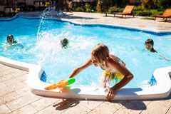 Cheerful children playing waterguns, rejoicing, jumping, swimming in pool. Copy space Stock Images