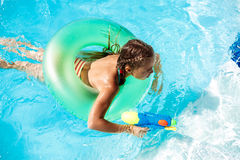 Cheerful children playing waterguns, rejoicing, jumping, swimming in pool. Copy space Royalty Free Stock Image