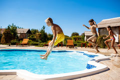 Cheerful children rejoicing, jumping, swimming in pool. Copy space Stock Images