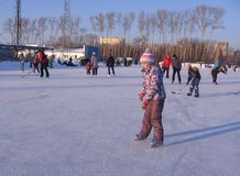 Cheerful children ride in the winter skating on the big rink stock photo