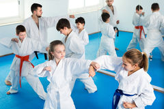 Cheerful children sparring in pairs. To practice new moves in karate class Stock Photo