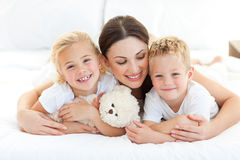 Cheerful children with their mother lying on a bed Royalty Free Stock Photography