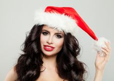 Cheerful Christmas Woman Wearing Santa Hat. Cute Girl Fashion Model with Makeup and Long Healthy Curly Hair Smiling Royalty Free Stock Photos
