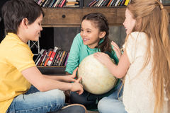 Cheerful classmates talking with globe in middle royalty free stock photos
