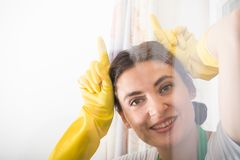 Cheerful cleaning woman acting funny. And washing the house window Royalty Free Stock Images